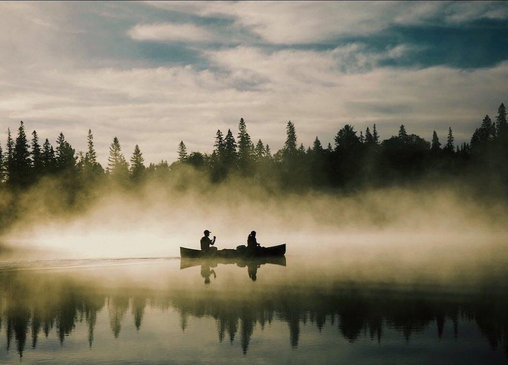 Two people paddling canoe on a misty morning on the lake