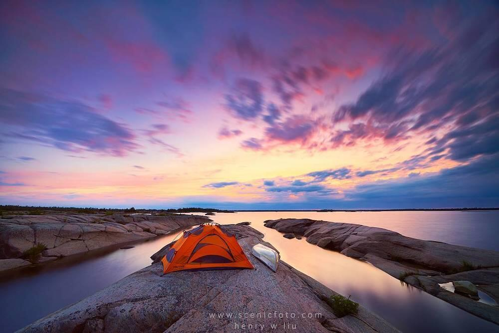 Tent set up near water with sunset