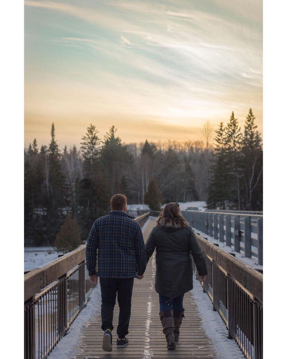 Couple holding hands while walking on boardwalk