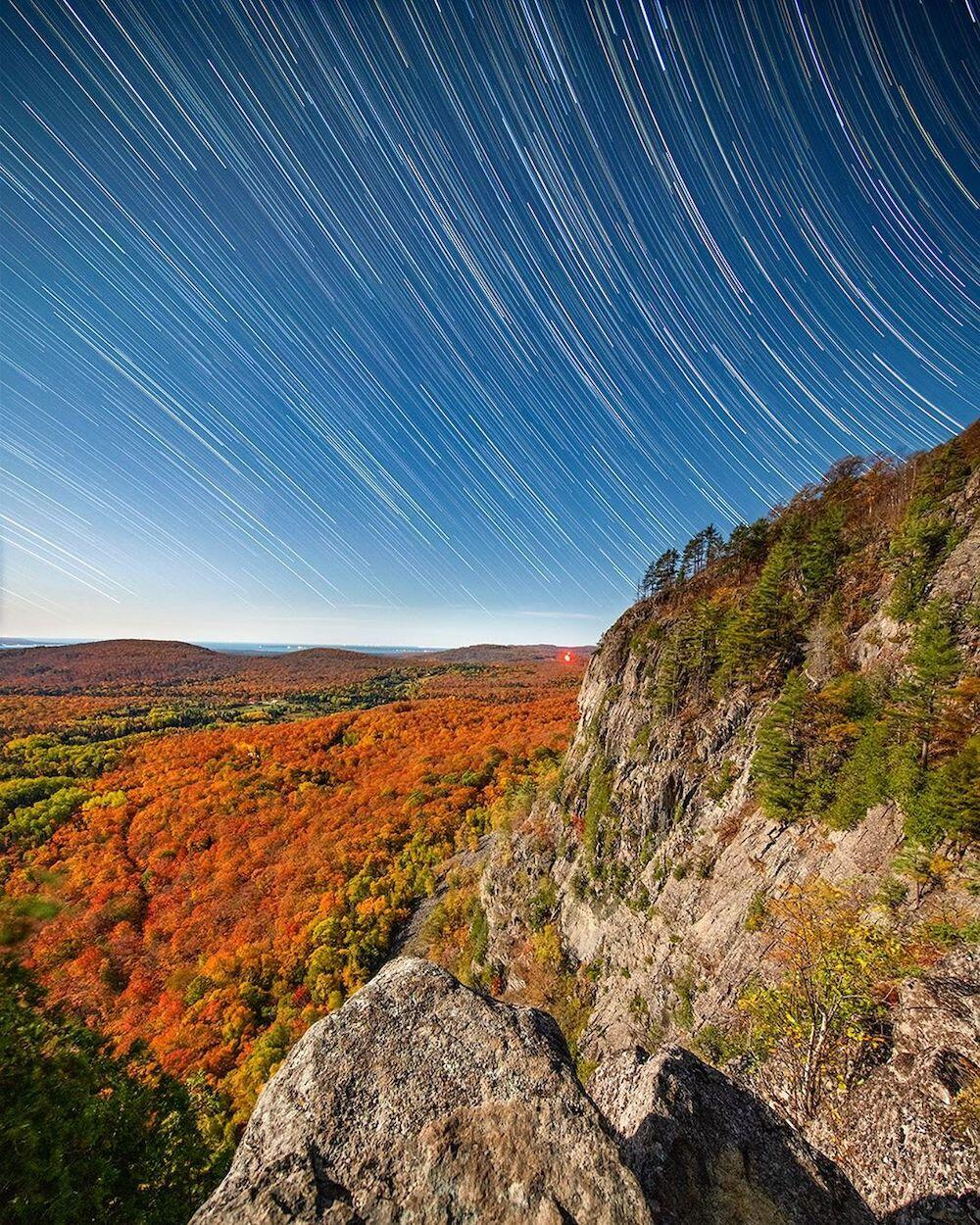 Cliff overlooking colourful trees with stars in sky