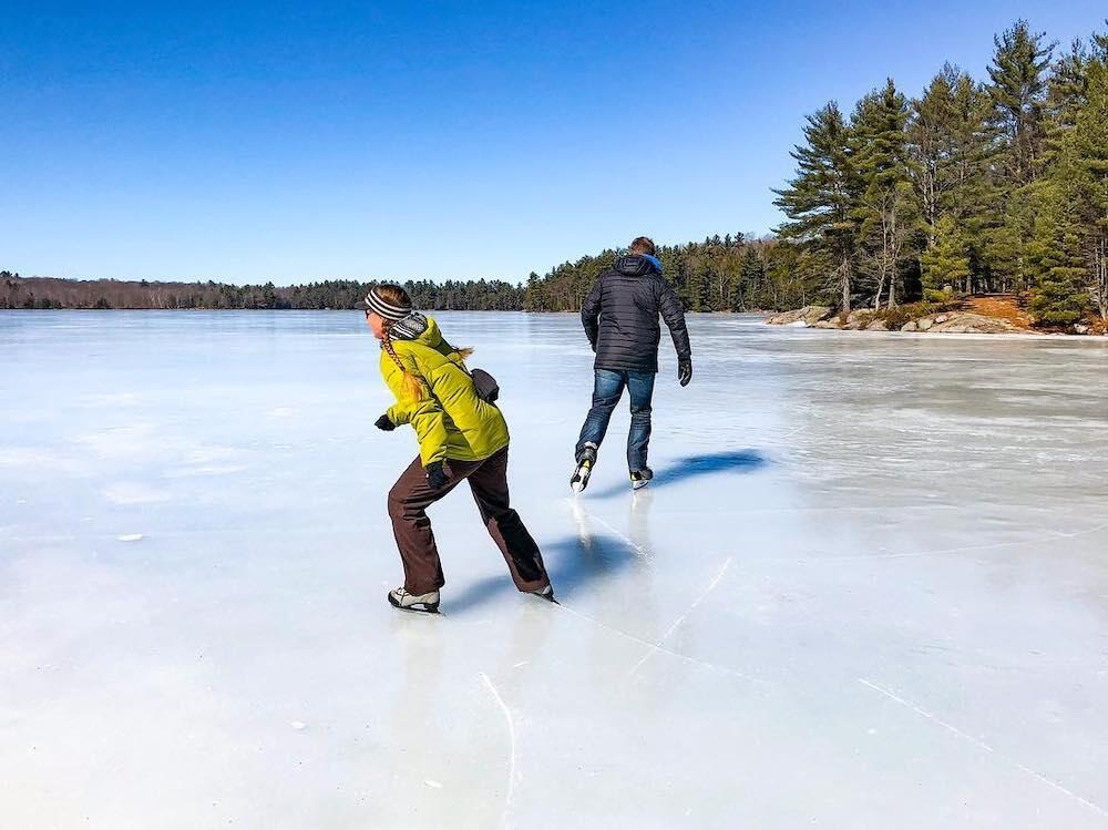 Two people skating on a lake