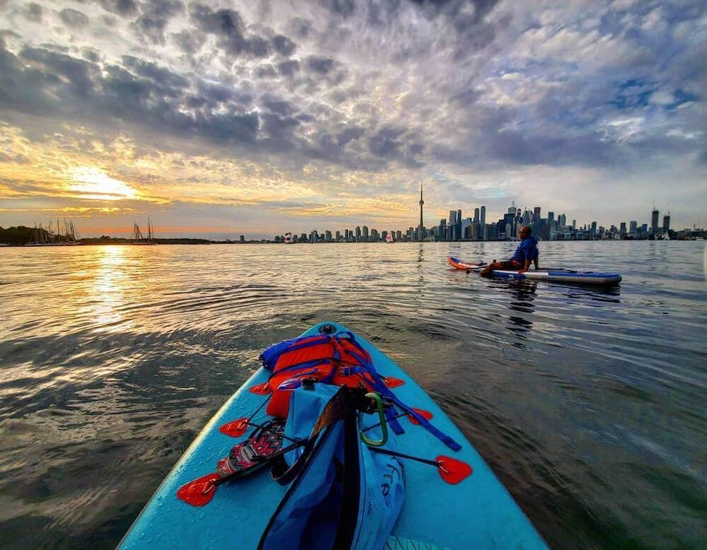 Two people paddleboarding with Toronto skyline in background