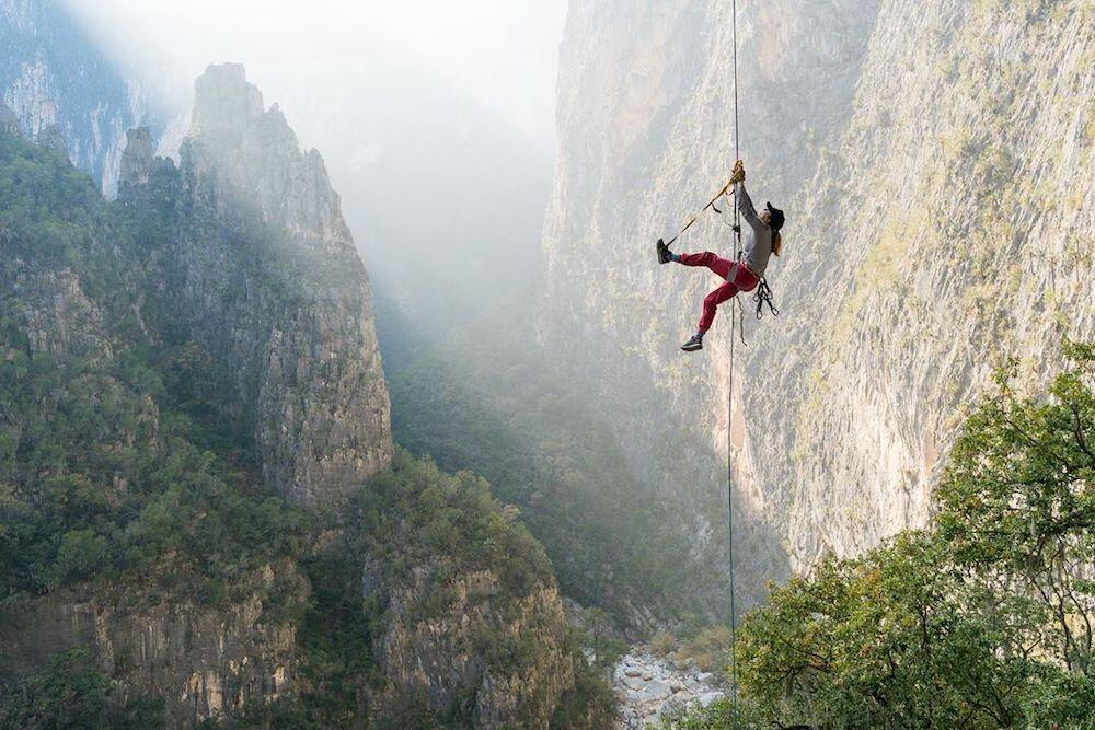Person hanging onto a rope beside a mountain