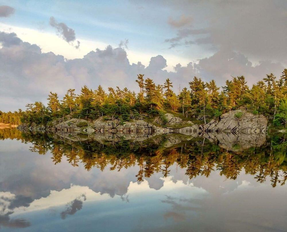 Trees and rocks reflected in lakewater.