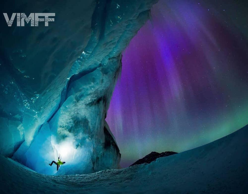 Someone ice-climbing with northern lights in background