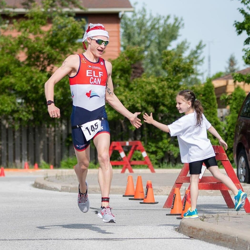 Male athlete in santa hat running on pavement in a race.
