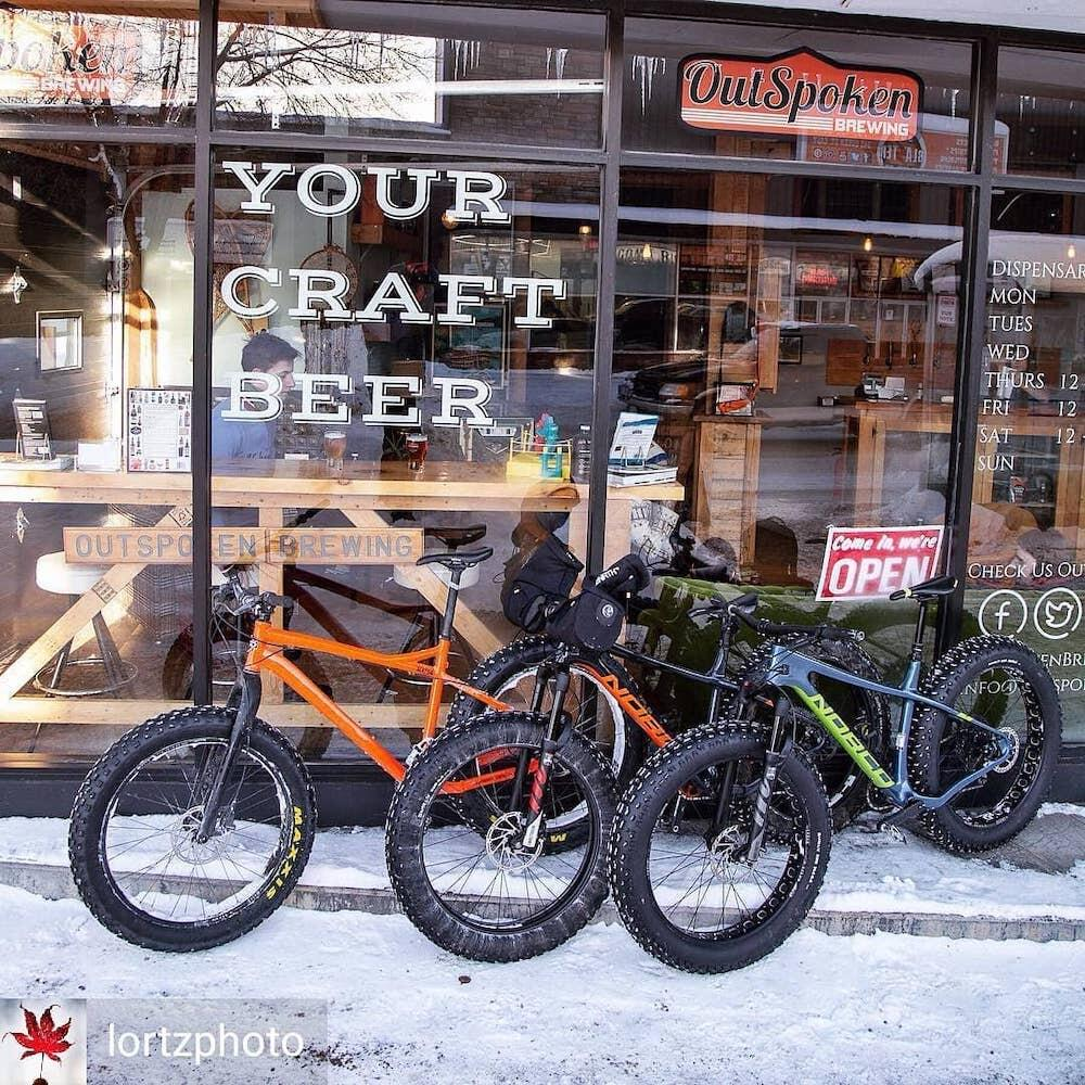 Bikes leaning up against shop window