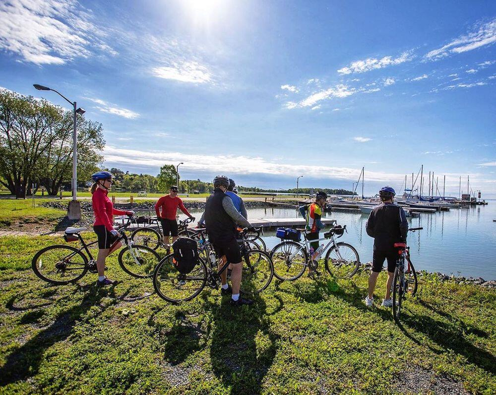 Cyclists gathered on grass next to harbour