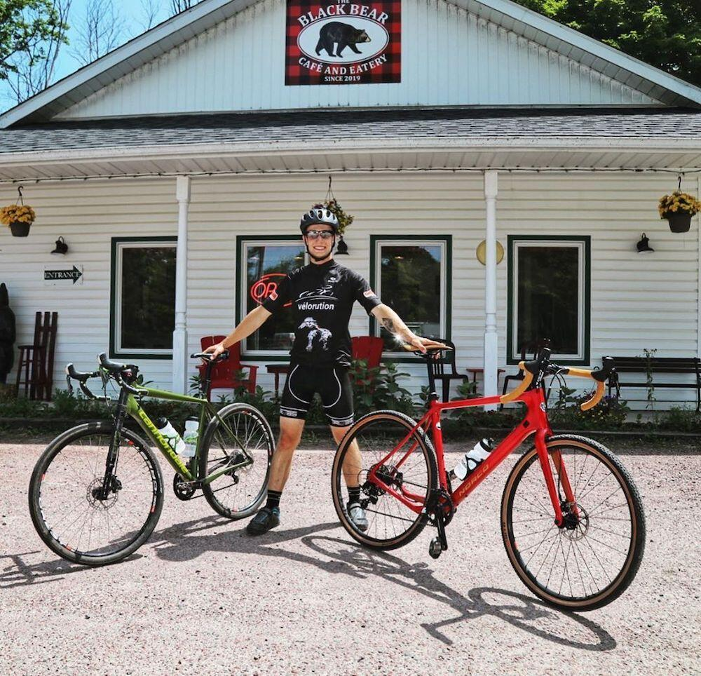 Person holding two bikes standing outside Black Bear Cafe and Eatery