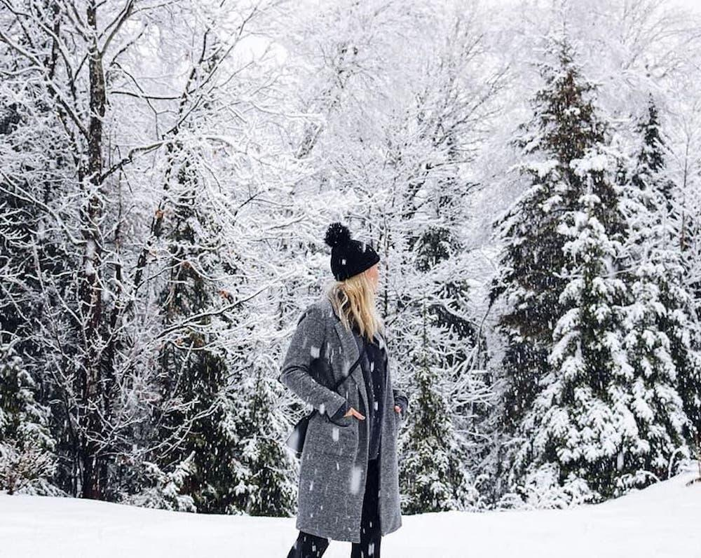 Woman walking among snow-covered trees.