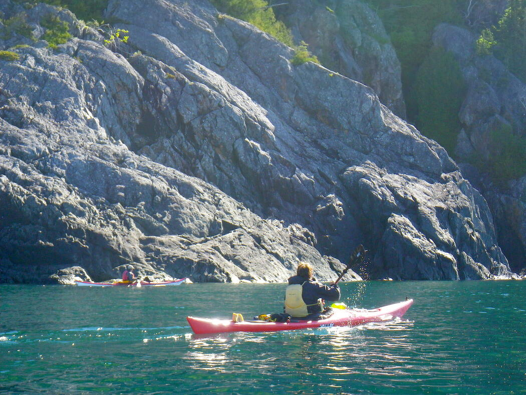 Sea kayaking paddling in turquoise waters near rock cliffs