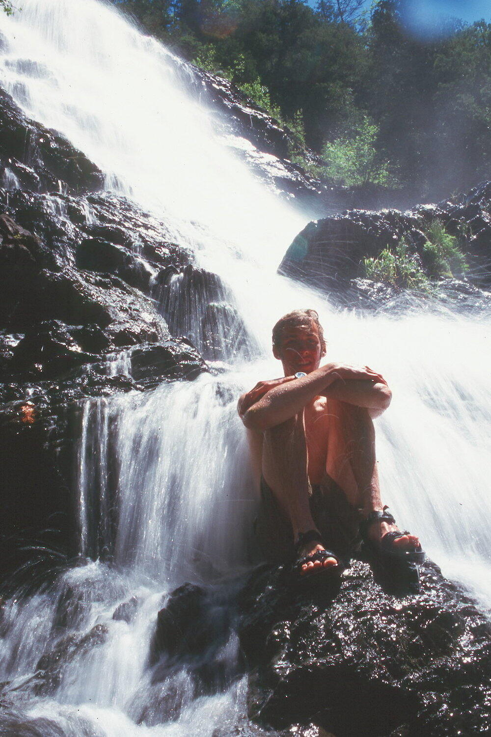 Man sitting on rock at bottom of waterfalls