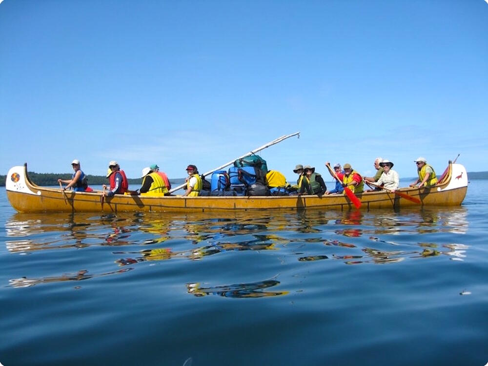 A group of people paddling a voyageur canoe.