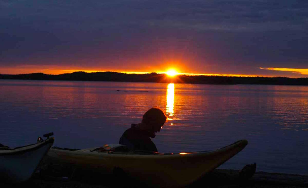 Man watching sunset while sitting on beach beside kayaks