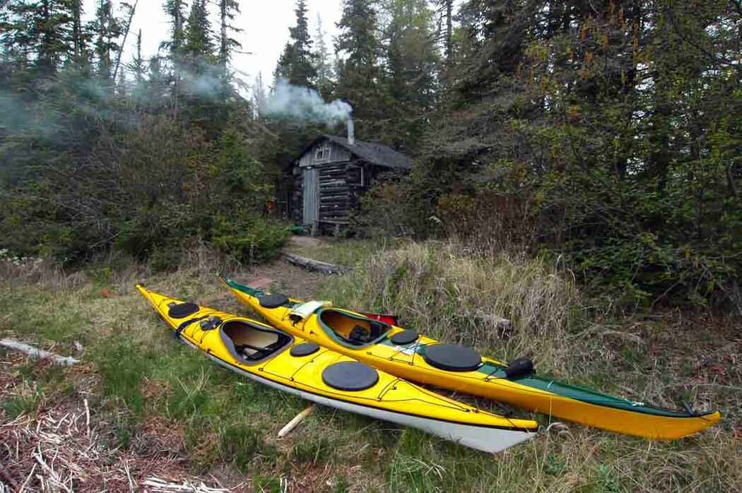 Two yellow kayaks in front of a wood fired sauna