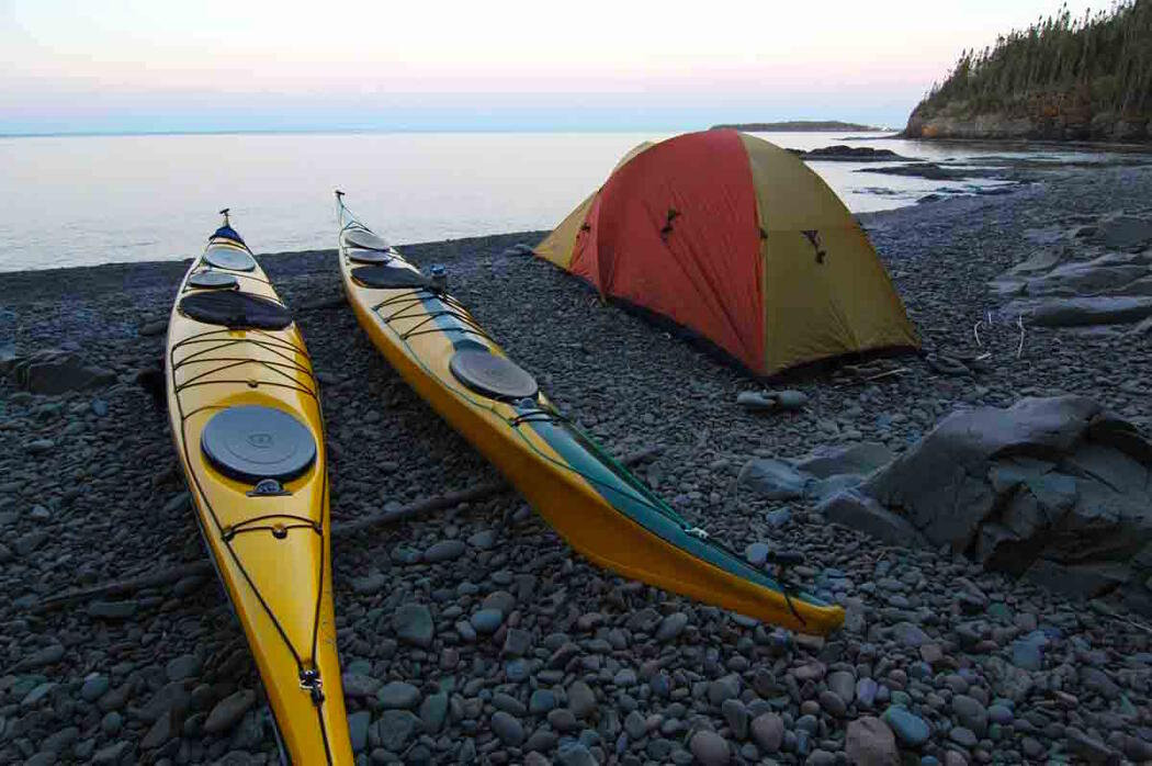 Two kayaks and a tent on stone beach