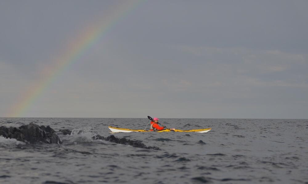Person sea kayaking with rainbow in sky