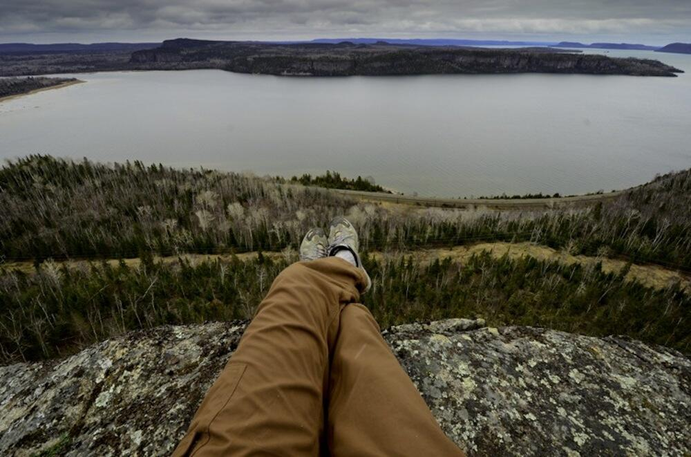 View of a hiker's legs and boots sitting on rock on vista over Lake Superior