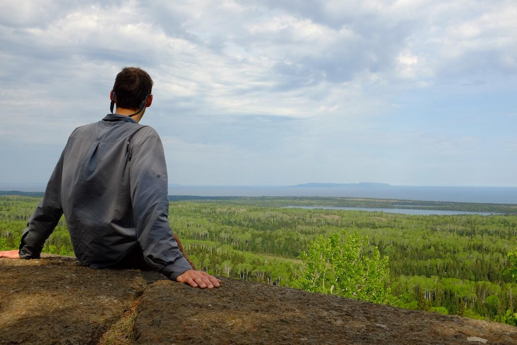 Back view of hiker sitting on a rock vista overlooking forest and Lake Superior