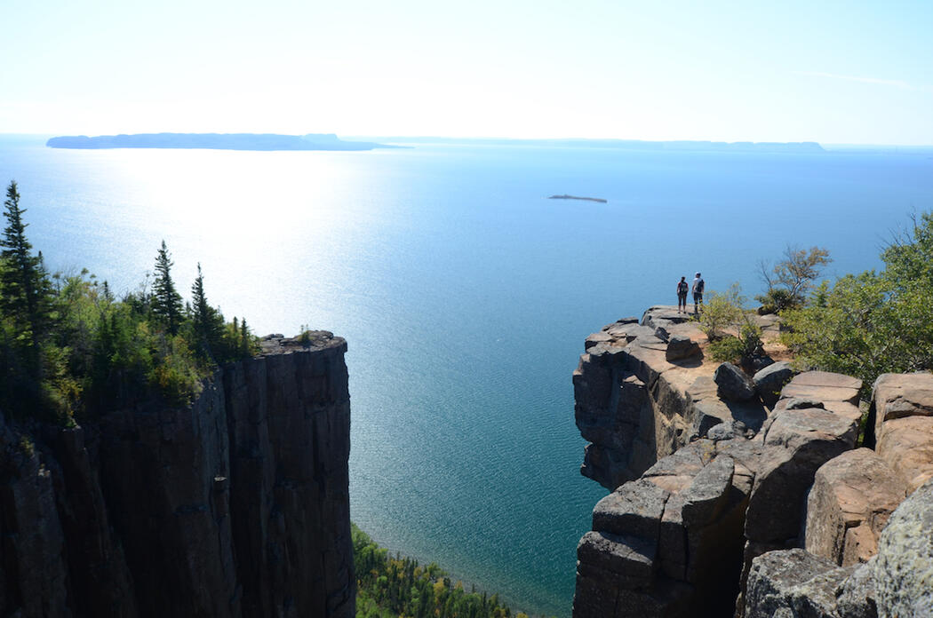 Panoramic view of two hikers standing on cliffs overlooking Lake Superior