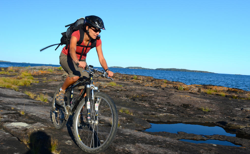 Woman riding a mountain bike over flat rocky surface with a lake in background.