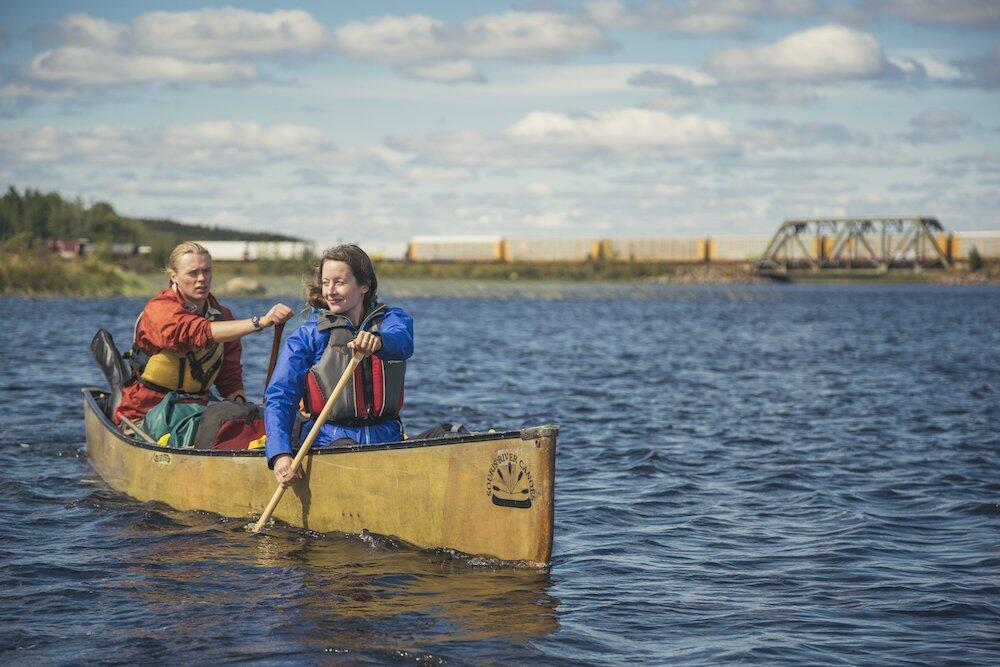Two people paddling canoe with bridge in background