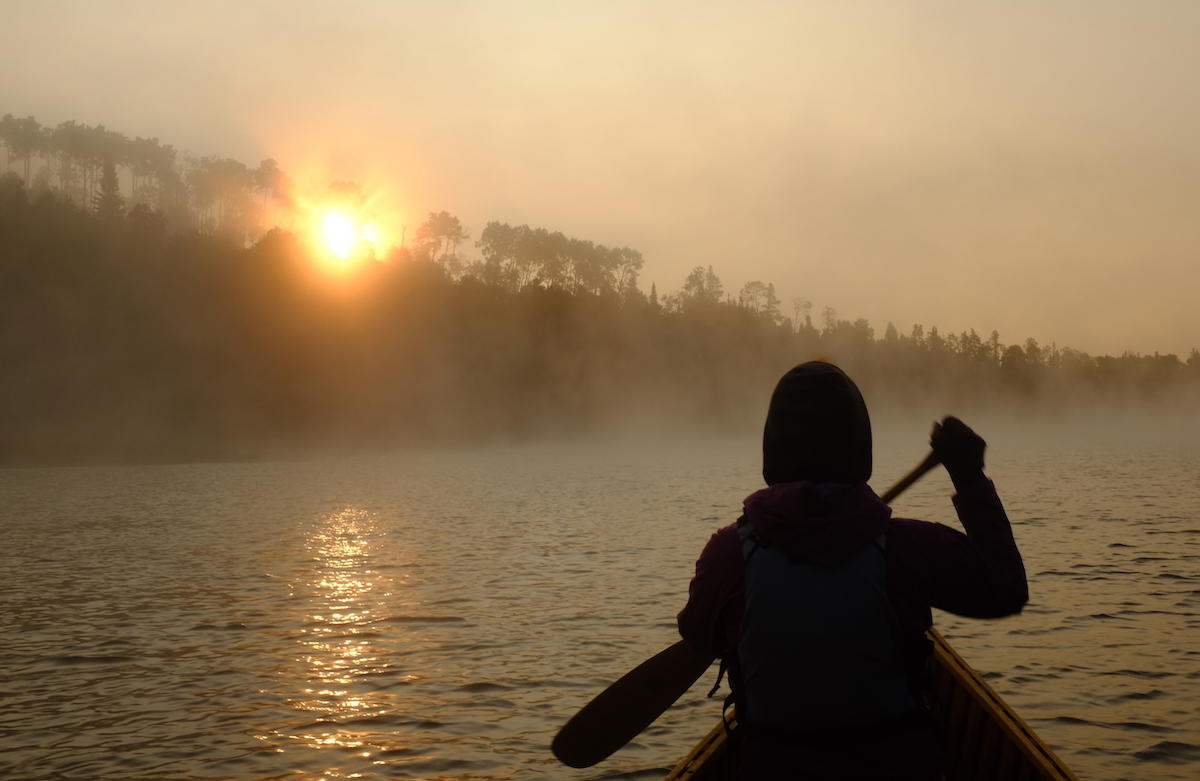 Canoeist paddling into sunrise on misty lake.