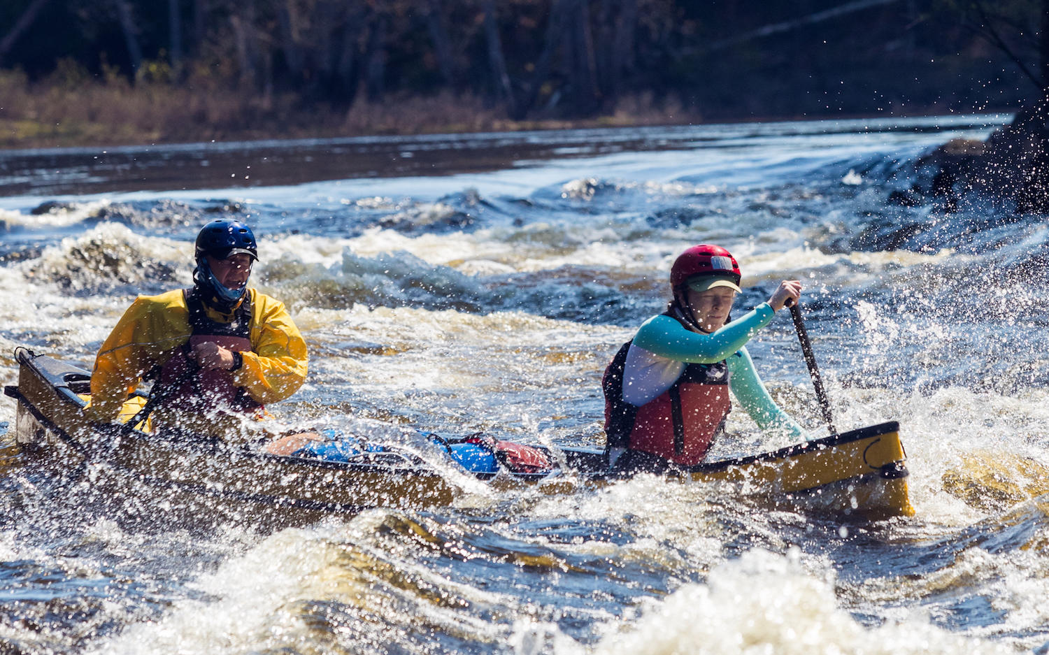 Father and Daughter paddling yellow canoe in big rapids