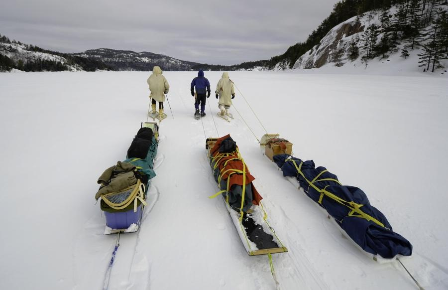 Three people, each pulling a toboggan packed with winter camping gear, on a frozen lake