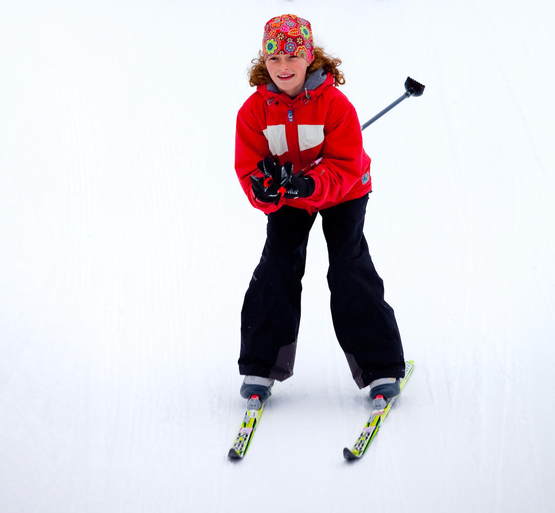 Young girl in tuck position while cross-country skiing.