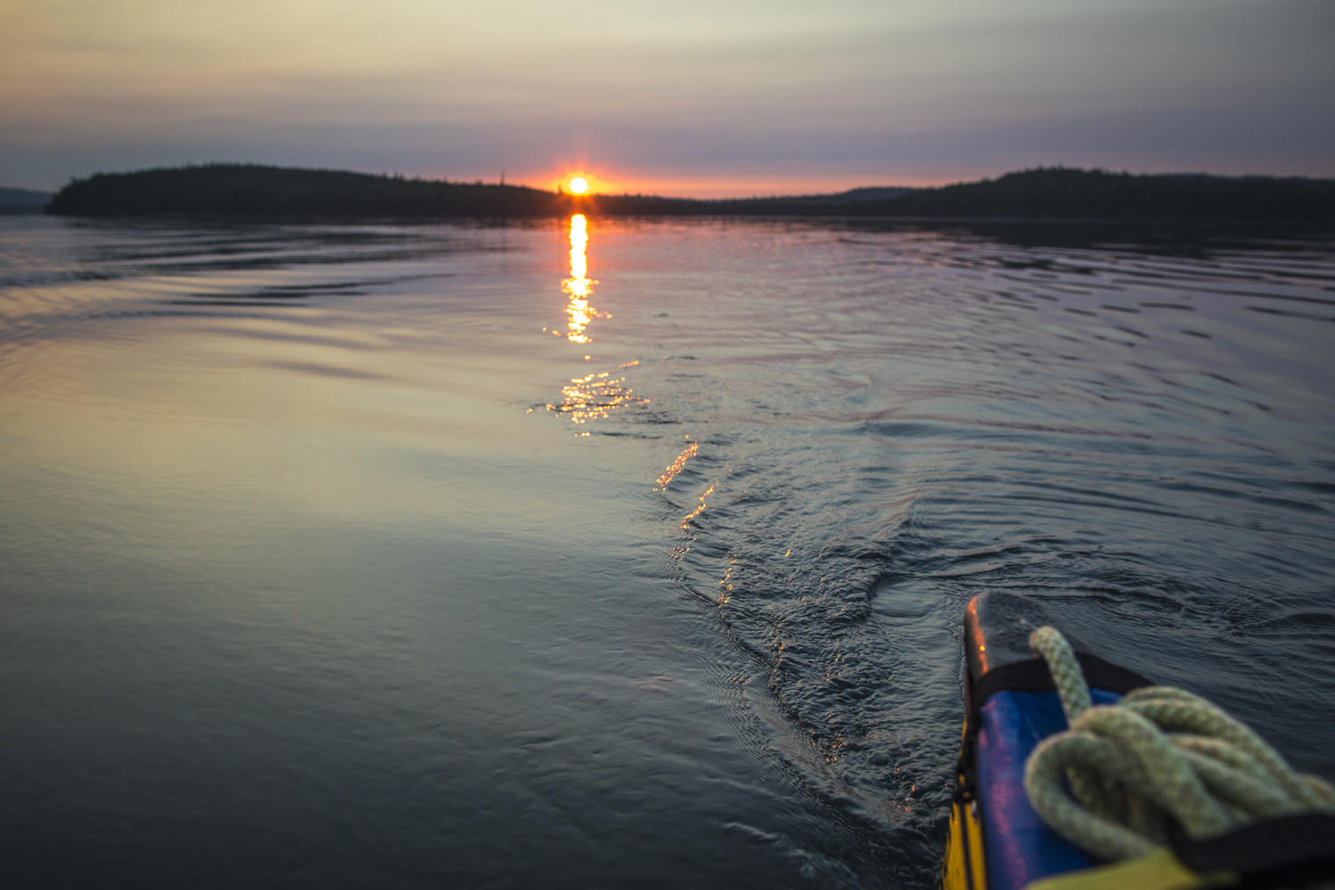 Looking back from stern of canoe into a sunset.