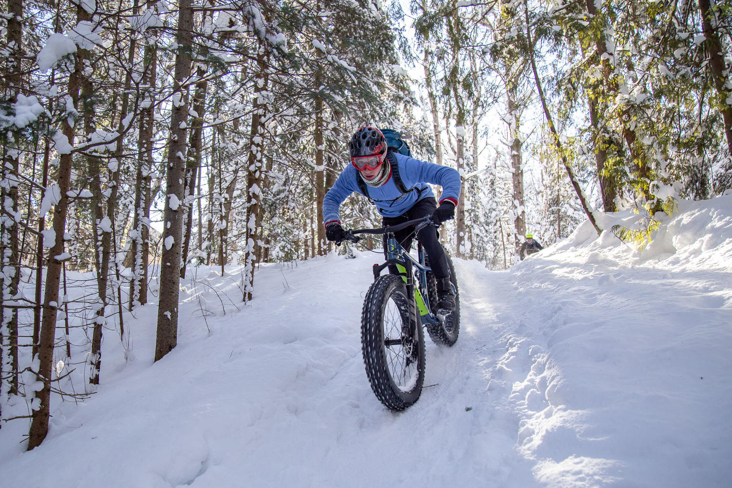 Man on fat tire bike cycling down a snow-covered hill in a forest.