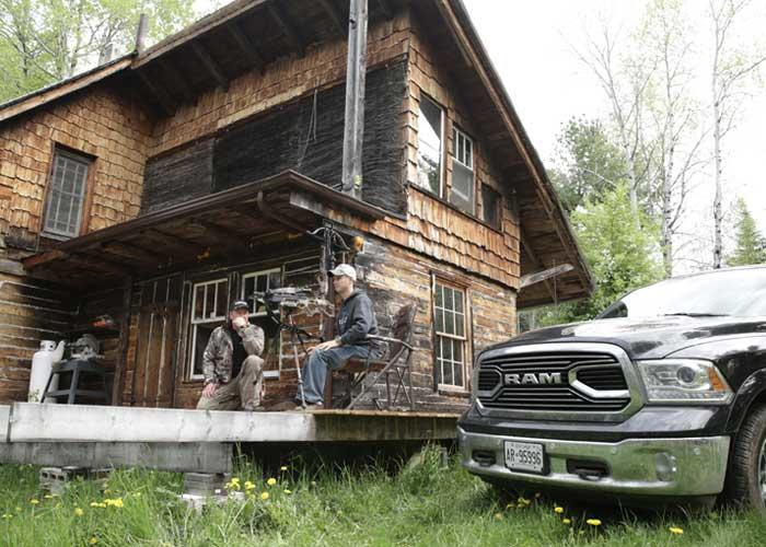 2 hunters sitting on cabin porch