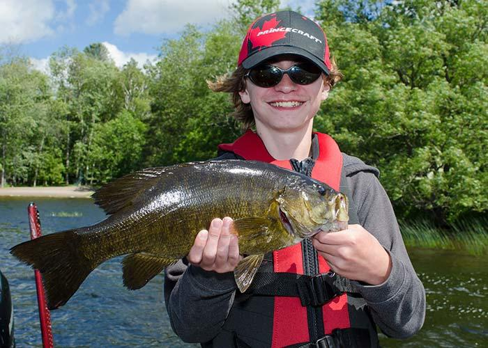 young boy holding smallmouth bass