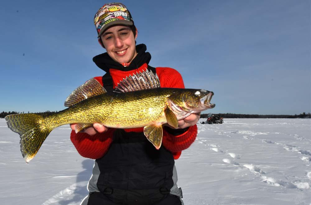 young male ice angler holding walleye