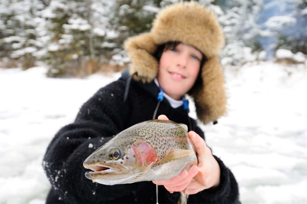 young ice angler holding trout