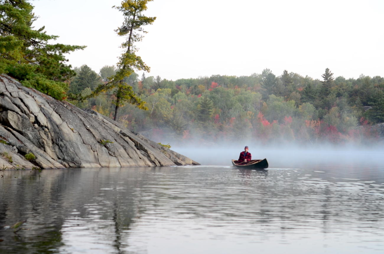 Canoeist paddling on misty lake