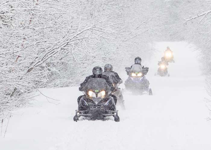 snowmobiles on snowy trail