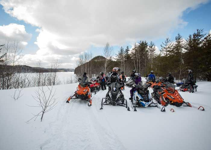 group of snowmobiles on trail