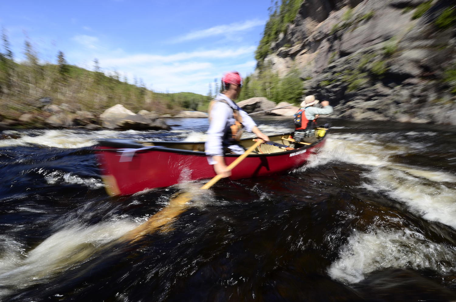 two paddlers in red canoe in whitewater