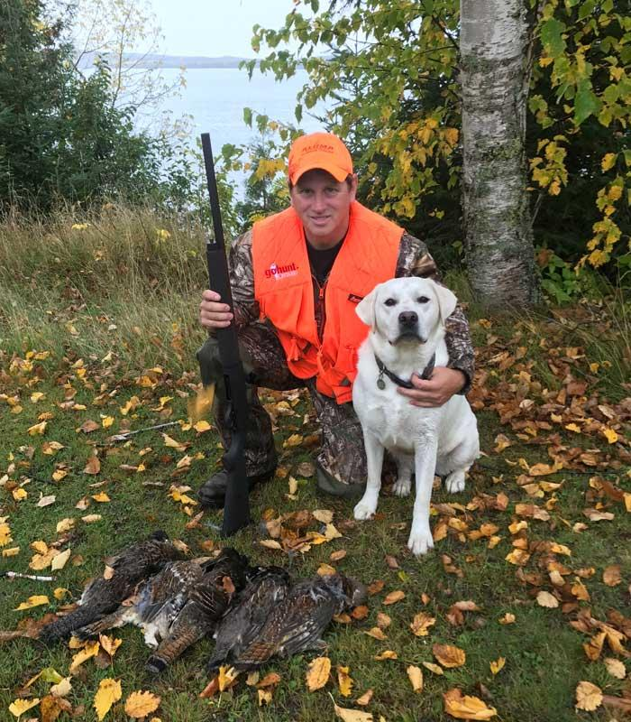 hunter and dog with harvested grouse