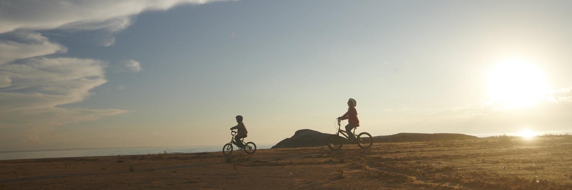 Outline of two kids riding bikes in distance on a flat landscape.