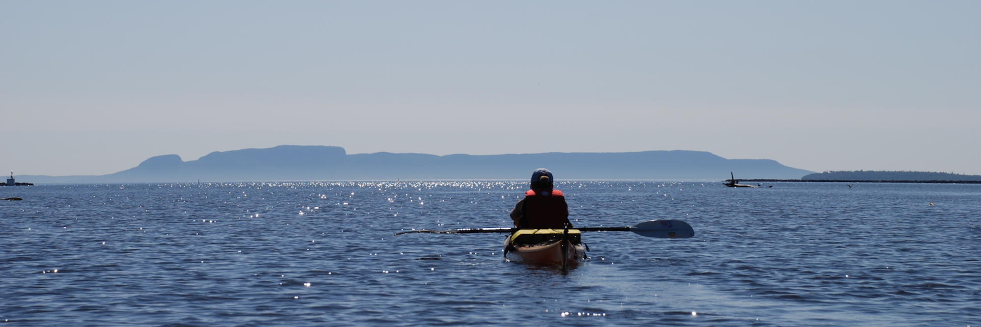 Kayaker paddling in front of Sleeping Giant