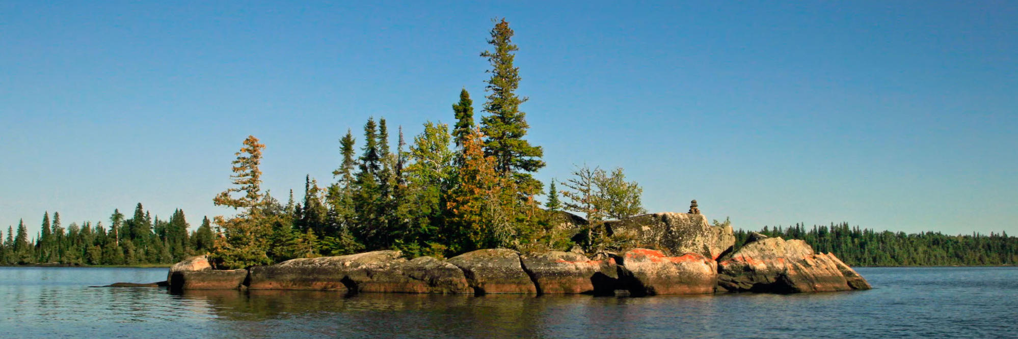 Small rock island with coniferous trees.