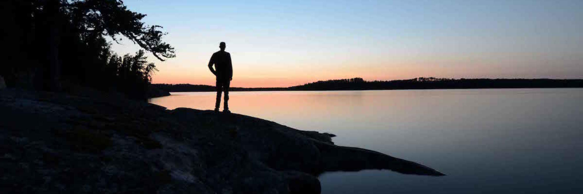Sillouette of a man standing on rocky shoreline of lake at sunset